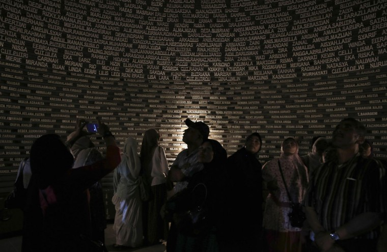Visitors look at the glowing names of tsunami victims at Aceh Tsunami Museum in Banda Aceh December 26, 2014. Survivors of Asia's 2004 tsunami and relatives of its 226,000 victims cried and prayed as they gathered along Indian Ocean shorelines on Friday for memorials to mark the 10th anniversary of a disaster that still leaves an indelible mark on the region. Hundreds gathered in Indonesia's Aceh province, many bursting into tears as poems and songs were heard and a montage was screened showing the devastation from a disaster that killed 126,741 people in Aceh alone. REUTERS/Beawiharta