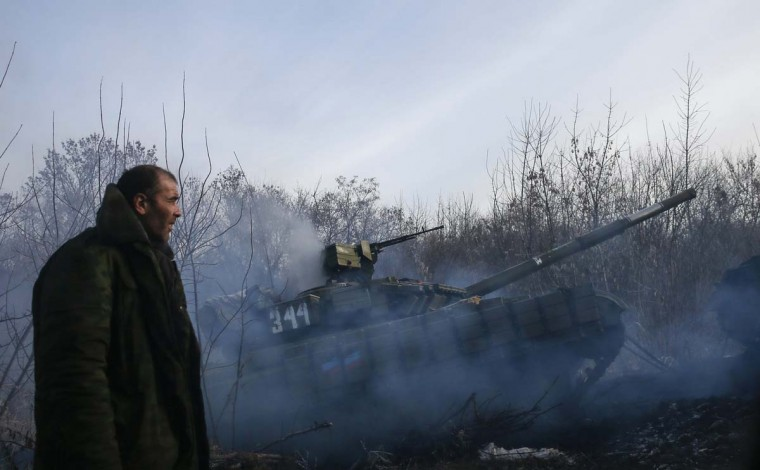 A man stands next to a pro-Russian separatist's tank riding near the village of Rozsypne (Rassypnoye), eastern Ukraine, December 15, 2014. (Maxim Shemetov/Reuters)