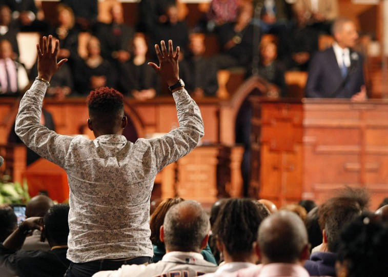 """A protestor with his hands up disrupts a speech by U.S. Attorney General Eric Holder (background R) at the Ebenezer Baptist Church during a forum titled """"The Community Speaks"""" in Atlanta, Georgia December 1, 2014. Holder said on Monday he would soon release new guidelines to limit racial profiling by federal law enforcement, a move long awaited by civil rights advocates. Holder announced his plan at Ebenezer Baptist Church in Atlanta, in the wake of unrest in Ferguson, Missouri following a grand jury's decision last week not to indict white police officer Darren Wilson in the killing of unarmed black teen Michael Brown. (REUTERS/Tami Chappell)"""