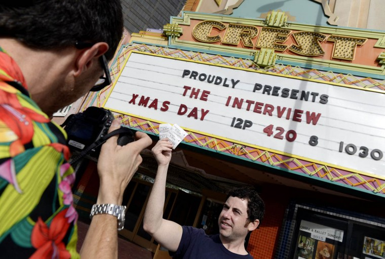 """Tickets for the film """"The Interview"""" is seen held up by a staff member for the media at Crest Theater in Los Angeles, California. Sony Pictures will allow """"The Interview"""" to play in more than 200 U.S. theaters as of Christmas Day, reversing its decision to pull the film, after coming under criticism from President Barack Obama and others for caving into pressure from North Korea. (Kevork Djansezian/Reuters photo)"""