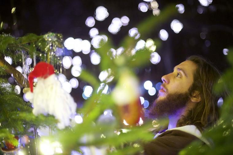 "Michael Grant, 28, ""Philly Jesus,"" adjusts Christmas ornaments with his walking staff at Rittenhouse Park in Philadelphia, Pennsylvania December 14, 2014. (Mark Makela/Reuters)"