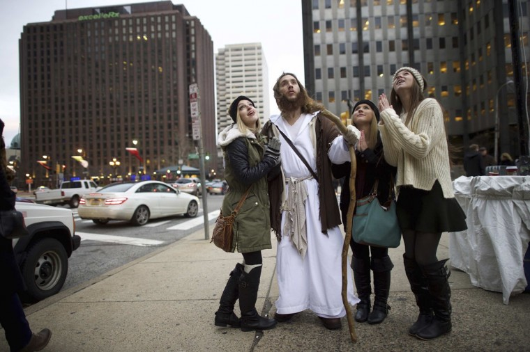 """Leah DeTommaso, 19, Alisyn Davidson, 19, and Taylor Moran, 18, ask to take a photograph with (center) Michael Grant, 28, """"Philly Jesus,"""" on December 14, 2014. (Mark Makela/Reuters)"""