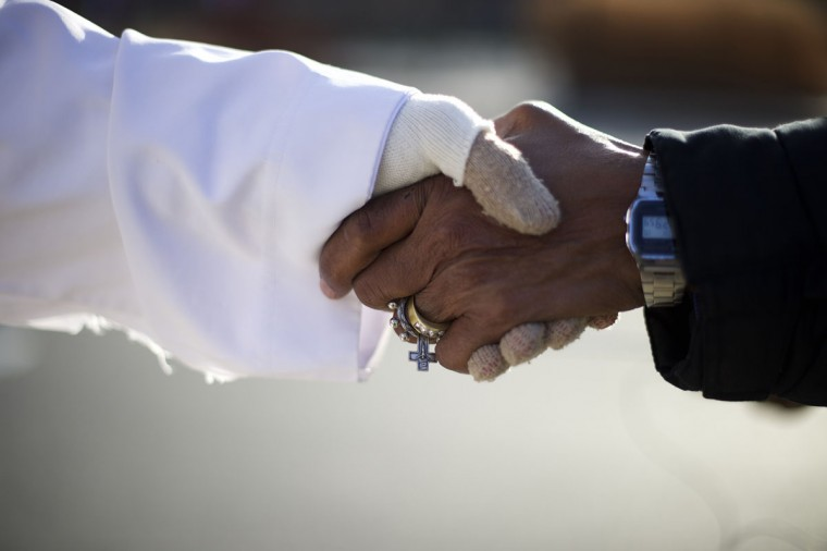 """Michael Grant, 28, """"Philly Jesus,"""" greets a pedestrian wearing a ring with a cross in Philadelphia, Pennsylvania December 18, 2014. (Mark Makela/Reuters)"""