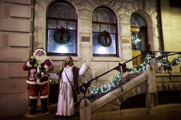 "Michael Grant, 28, ""Philly Jesus,"" poses for a portrait beside a sculpture of Santa Claus in Philadelphia, Pennsylvania December 14, 2014. (Mark Makela/Reuters)"