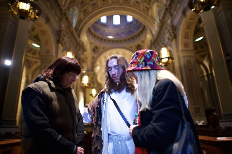 """(L-R) Christine Tyson and JoAnne Gilley pray with Michael Grant, 28, """"Philly Jesus,"""" inside Cathedral Basilica of Saints Peter and Paul in Philadelphia, Pennsylvania December 18, 2014. (Mark Makela/Reuters)"""