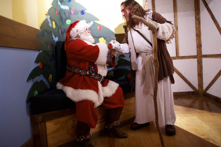"""Michael Grant, 28, """"Philly Jesus,"""" greets Santa Claus at Macy's department store in Philadelphia, Pennsylvania December 18, 2014. (Mark Makela/Reuters)"""