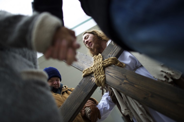 """Jayden Hensley, 39, (L) prays with Michael Grant, 28, """"Philly Jesus,"""" before he carried a 12 foot cross 8 miles through North Philadelphia to LOVE Park in Center City as part of a Christmas walk to spread the true message of the holiday in Philadelphia, Pennsylvania December 20, 2014. As many as a half dozen others joined him for numerous miles as he trekked southward down Broad Street. Some shouted """"Praise Jesus!"""" and """"Thank you for doing this!"""" at the sight. (Mark Makela/Reuters)"""