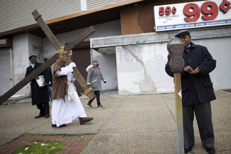 """A man puts change into a parking meter as Michael Grant, 28, """"Philly Jesus,"""" carries a 12 foot cross 8 miles through North Philadelphia to LOVE Park in Center City as part of a Christmas walk to spread the true message of the holiday in Philadelphia, Pennsylvania December 20, 2014. (Mark Makela/Reuters)"""