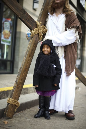 """Casey Green, 4, poses with Michael Grant, 28, """"Philly Jesus,"""" in a break from his carrying a 12 foot cross 8 miles through North Philadelphia to LOVE Park in Center City as part of a Christmas walk to spread the true message of the holiday in Philadelphia, Pennsylvania December 20, 2014. (Mark Makela/Reuters)"""