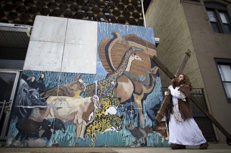 """Michael Grant, 28, """"Philly Jesus,"""" carries a 12 foot cross 8 miles past a mural depicting Noah's Ark in North Philadelphia towards LOVE Park in Center City as part of a Christmas walk to spread the true message of the holiday in Philadelphia, Pennsylvania December 20, 2014. (Mark Makela/Reuters)"""