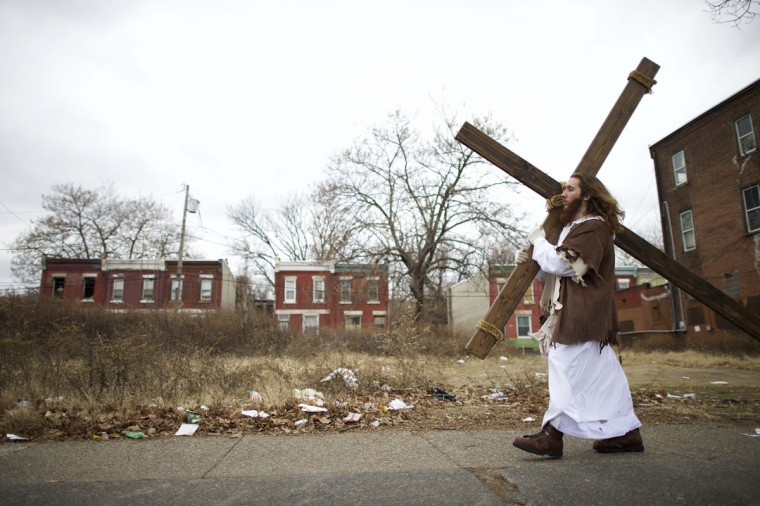 """Michael Grant, 28, """"Philly Jesus,"""" carries a 12 foot cross 8 miles through this blighted area of North Philadelphia towards LOVE Park in Center City as part of a Christmas walk to spread the true message of the holiday in Philadelphia, Pennsylvania December 20, 2014. (Mark Makela/Reuters)"""