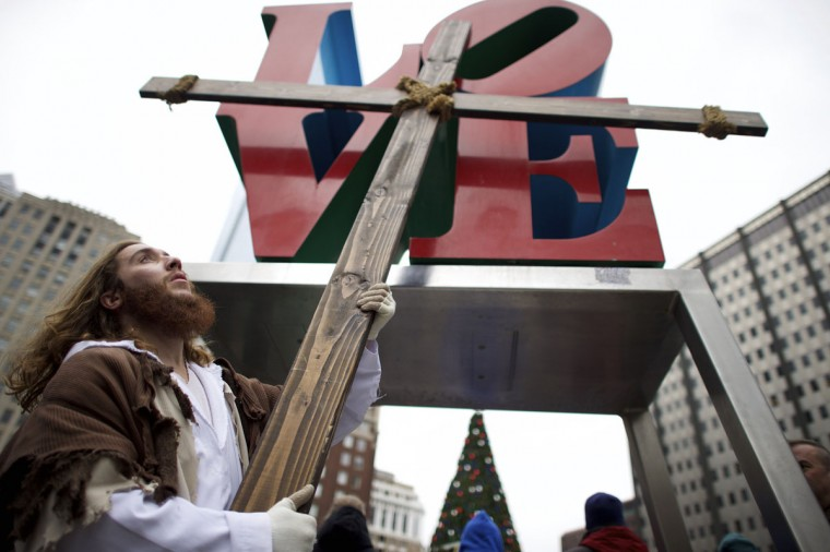 """Upon reaching LOVE Park in Center City, Michael Grant, 28, """"Philly Jesus,"""" lifts the 12 foot cross he had carried 8 miles through North Philadelphia as part of a Christmas walk to spread the true message of the holiday in Philadelphia, Pennsylvania December 20, 2014. (Mark Makela/Reuters)"""
