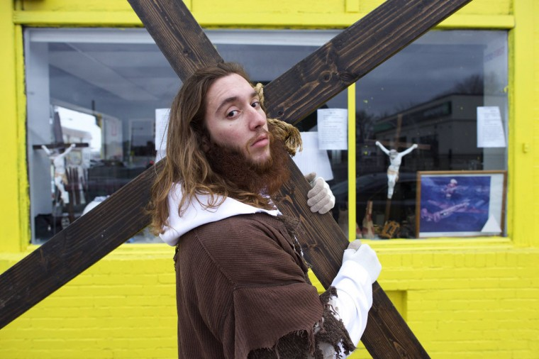 """Michael Grant, 28, """"Philly Jesus,"""" poses for a portrait in front of a store window featuring crucifixes with the 12 foot cross he carried 8 miles through North Philadelphia to LOVE Park in Center City as part of a Christmas walk to spread the true message of the holiday in Philadelphia, Pennsylvania December 20, 2014. (Mark Makela/Reuters)"""