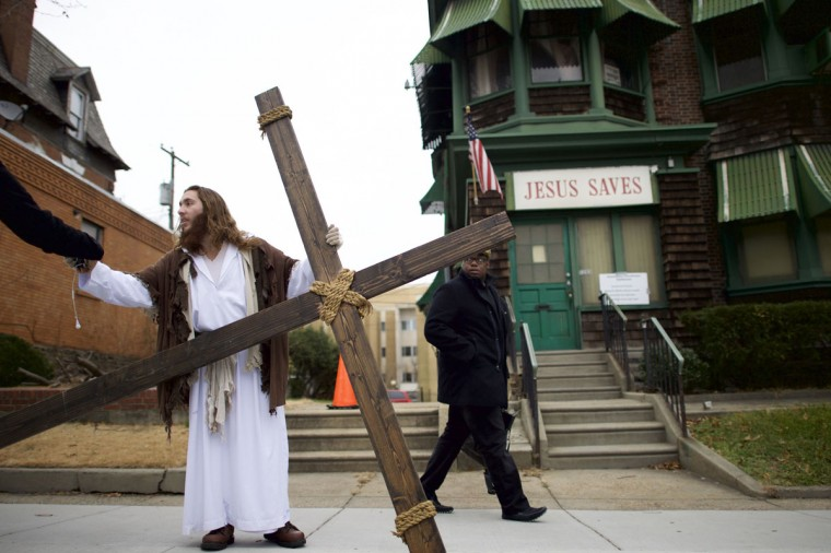 """As a pedestrian looks on, Michael Grant, 28, """"Philly Jesus,"""" hands a supporter his iPhone and headphones after saying goodbye to a friend, while holding a 12 foot cross which he carried 8 miles through North Philadelphia to LOVE Park in Center City as part of a Christmas walk to spread the true message of the holiday in Philadelphia, Pennsylvania December 20, 2014. (Mark Makela/Reuters)"""