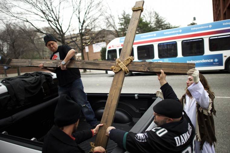 """Supporters (L-R) Jason Krieck, 38, Ryan Bolli, 42, and Nando Fuselli, 38, assist Michael Grant, 28, """"Philly Jesus,"""" in lashing the 12 foot cross to a truck following his 8 miles cross walk through North Philadelphia to Center City as part of a Christmas walk to spread the true message of the holiday in Philadelphia, Pennsylvania December 20, 2014. (Mark Makela/Reuters)"""