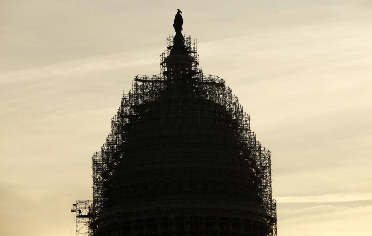 A worker (L) reaches for supplies while working atop the scaffolded dome of the U.S. Capitol in Washington December 4, 2014. The Capitol Dome is undergoing a multi-year restoration to stop the current level of deterioration in the Dome's cast iron as well as ensuring the protection of the interior of the Dome and Rotunda. The restoration project includes removal of old paint, repairs to the cast iron and stone, and repainting. REUTERS/Kevin Lamarque