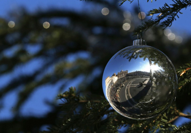 Saint Peter's Square is reflected on an ornamental ball on a tree as Pope Francis leads the Angelus prayer at the Vatican December 26, 2014. REUTERS/Alessandro Bianchi