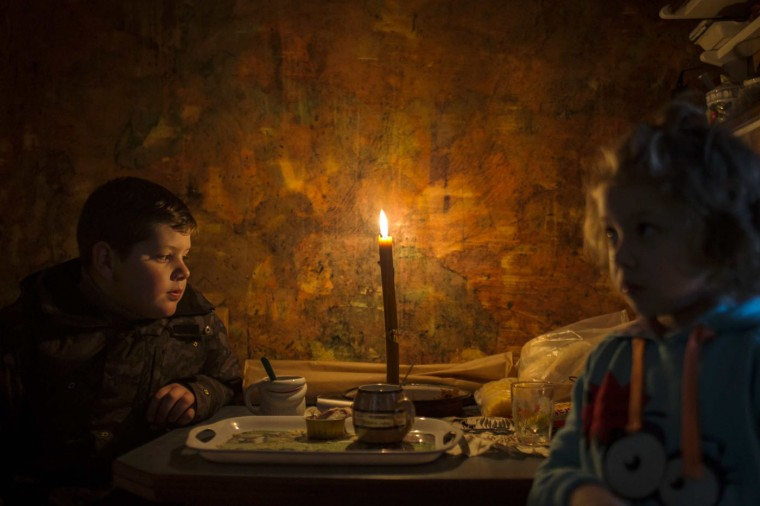 Lazar and his sister Andjelka sit by a candle in their home in the eastern Serbian town of Majdanpek, December 4, 2014. Electricity workers in Serbia struggled through snow, ice and treacherous terrain on Thursday to restore electricity to an eastern town left shivering without power, heating or running water for a fourth day. REUTERS/Marko Djurica