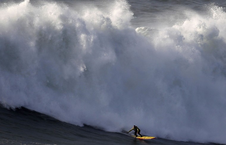 Big-wave surfer Garrett McNamara drops in on a large wave at Praia do Norte in Nazare January 29, 2013. McNamara of Haleiwa, Hawaii, who won the Biggest Wave title at the 2012 Billabong XXL Big Wave Awards with his world record 78-foot (24-metre) wave ridden at Praia do Norte on November 1, 2011. McNamara has returned to Nazare because he wants to try to beat the record again, and the forecast for the next days are of big waves. (REUTERS/Rafael Marchante)