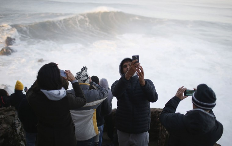 People gather to watch a tow-in surfing session at Praia do Norte, in Nazare December 11, 2014. Praia do Norte beach has gained popularity with big wave surfers since Hawaiian surfer Garrett McNamara broke a world record for the largest wave surfed here in 2011. (REUTERS/Rafael Marchante)