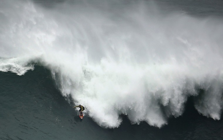 Big-wave surfer Garrett McNamara of the U.S. drops in on a large wave at Praia do Norte, in Nazare November 1, 2013. McNamara, who lives in Haleiwa, Hawaii, won the Biggest Wave title at the 2012 Billabong XXL Big Wave Awards with his world record 78-foot (24-metre) wave ridden at Praia do Norte, Nazare, Portugal on November 1, 2011. McNamara has returned to Nazare because he wants to try to beat the record again. (REUTERS/Rafael Marchante)