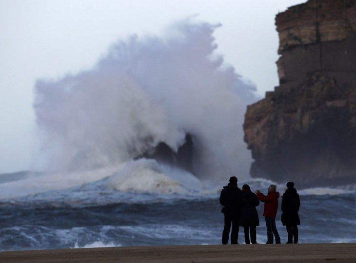 People take pictures of large waves at Nazare beach, December 25, 2013. (REUTERS/Hugo Correia)