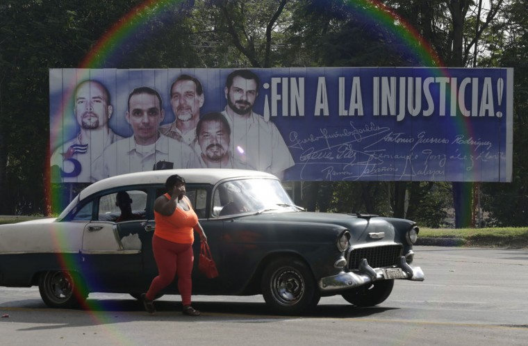 "A woman walks near a car in front of a banner featuring five Cuban prisoners held in U.S. custody, two of whom were previously released, in Havana December 17, 2014. U.S. President Barack Obama was set to announce a shift in policy toward Cuba on Wednesday and the Associated Press reported the changes would include the opening of an embassy in Cuba and the start of talks to normalize relations. The shift in policy, which could be one of the biggest changes in decades of animosity between communist-ruled Cuba and the United States, was heralded by Cuba's release of American aid worker Alan Gross after five years in prison in a reported prisoner exchange with Havana. CNN reported a prisoner exchange that also included Cuba's release of a U.S. intelligence source and the U.S. release of three Cuban intelligence agents. The banner reads, ""end of injustice!"". REUTERS/Enrique De La Osa"