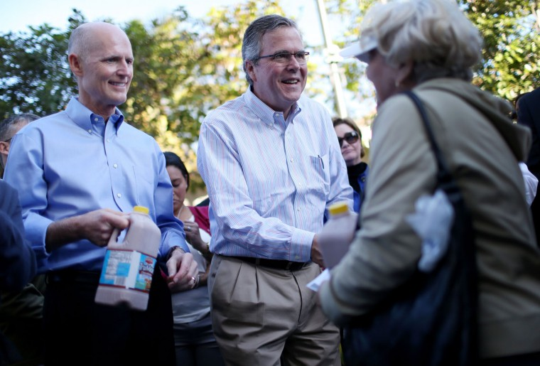Florida Governor Rick Scott (L) and Former Florida Governor Jeb Bush hand out items for Holiday Food Baskets to those in need outside the Little Havana offices of CAMACOL, the Latin American Chamber of Commerce on December 17, 2014 in Miami, Florida. Both governors reacted as they gave out food to the annoucement that the United States and Cuba worked out a deal for the release of USAID subcontractor Alan Gross. (Photo by Joe Raedle/Getty Images)