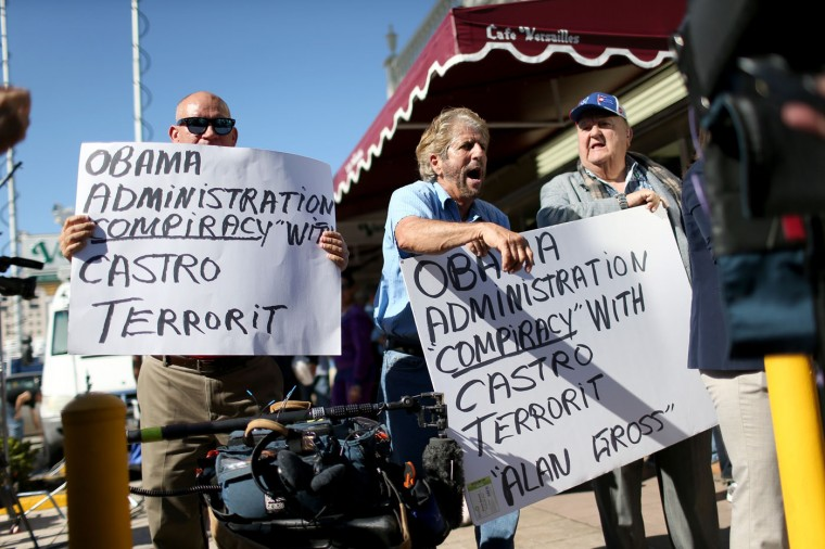 Osvaldo Hernadez, Miguel Saavedra and Carlos Munoz Fontanillehas (L-R) react to the news, outside the Little Havana restaurant Versailles, that Alan Gross was released from a Cuban prison on December 17, 2014 in Miami, United States. Alan Gross, the American contractor had spent five years in Cuban jail and reports indicate he is on his way back to the United States. (Photo by Joe Raedle/Getty Images)