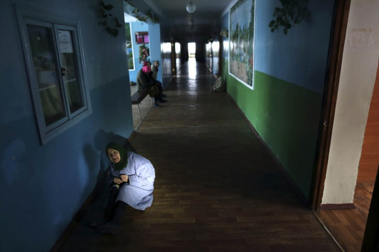 """Patients are seen in a hallway at the regional psycho-neurological hospital on the outskirts of Slovyanoserbsk, in a territory controlled by """"Lugansk People's Republic"""" (LPR), eastern Ukraine, December 1, 2014. The Psycho-Neurological Hospital outside the village of Slovyanoserbsk is caught in the crossfire in separatist-held territory about 30 km (20 miles) northwest of the rebel stronghold of Luhansk and near the frontline. Medical workers say the head of the hospital was killed by a shell in Luhansk and about half the 180 staff have fled. There were 400 patients when fighting began, they say. (Antonio Bronic/Reuters photo)"""