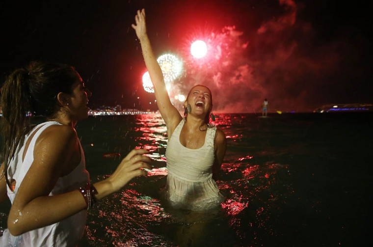 Revelers celebrate as fireworks explode during New Year's festivities on Copacabana Beach on January 1, 2015 in Rio de Janeiro, Brazil. Up to 2 million revelers were expected on Copacabana Beach to watch the annual New Year's fireworks display which this year coincided with the start of the city's 450th anniversary celebrations. (Mario Tama/Getty Images)