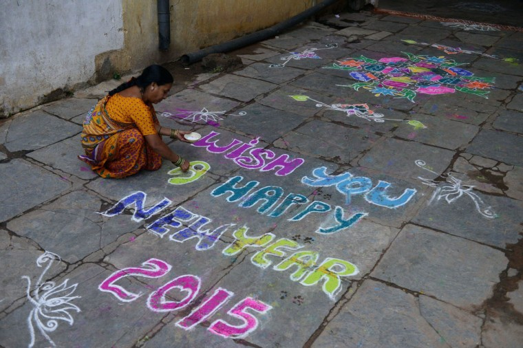 "An Indian woman applies coloured powder to a ""rangolis"", a Hindu ritual design, in front of her home in Hyderabad on January 1, 2015. Rangolis are drawn in front of homes early in the morning with a beautiful motif to welcome relatives and friends to mark the New Year. (Noah Seelam/Getty Images)"