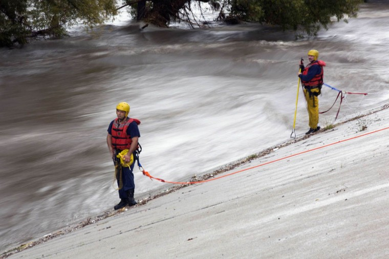 Los Angeles Fire Department personnel stand by next to the Los Angeles river during a rescue operation in Los Angeles, California December 12, 2014. A Pacific storm pounded Southern California with heavy rain and high winds on Friday, triggering flash floods and mudslides that prompted the evacuation of hundreds of homes, damaged dozens of others and disrupted passenger rail service along the coast. (Mario Anzuoni/Reuters photo)