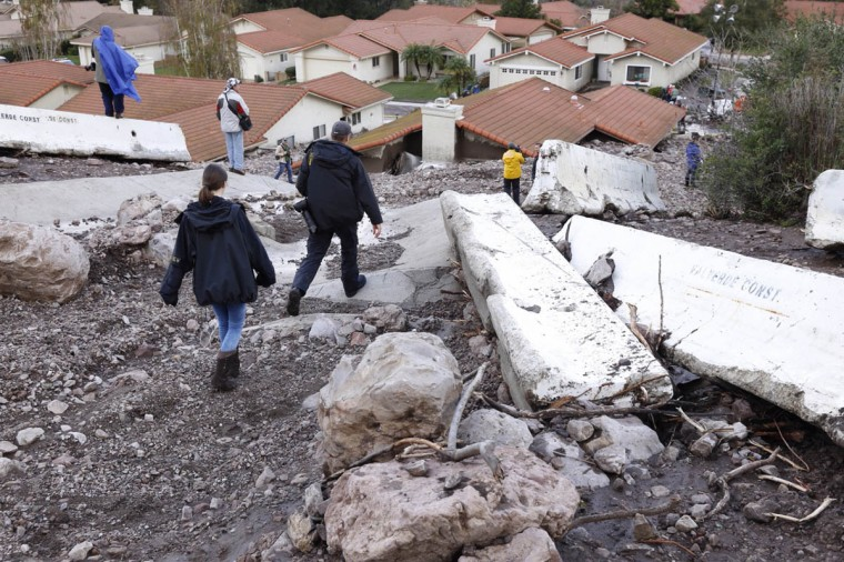 Media look at the debris flow that filled homes and backyards along San Como Lane on Dec. 12, 2014 in Camarillo Springs, Calif. (Al Seib/Los Angeles Times)