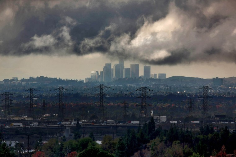 The Los Angeles downtown skyline appears on the horizon as clouds give way to sunlight Friday, Dec. 12, 2014, viewed from Sierra Madre Avenue in Azusa, Calif. (Irfan Khan/Los Angeles Times)