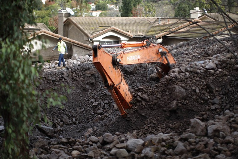 Part of a large backhoe is exposed as workers retrieve the machine that was buried under rocks and mud during a attempt to save homes from debris flows overnight as a powerful storm that has been lashing northern California moves southward on December 12, 2014 in Camarillo Springs neighborhood of Camarilla, California. (David McNew/Getty Images)