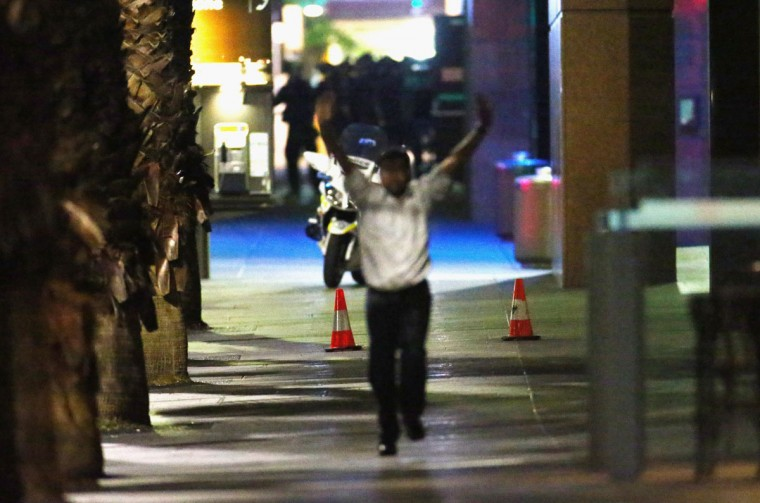 A hostage runs down Philip street after coming out of the Lindt Cafe, Martin Place on December 15, 2014 in Sydney, Australia. Police attend a hostage situation at Lindt Cafe in Martin Place. (Photo by Don Arnold/Getty Images)