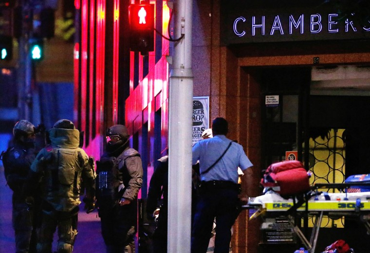 Anti-explosive police officers talk next to the Lindt Cafe, Martin Place during a hostage standoff on December 16, 2014 in Sydney, Australia. Police stormed the Sydney cafe after a gunman had taken hostages, ending the standoff. (Photo by Daniel Munoz/Getty Images)