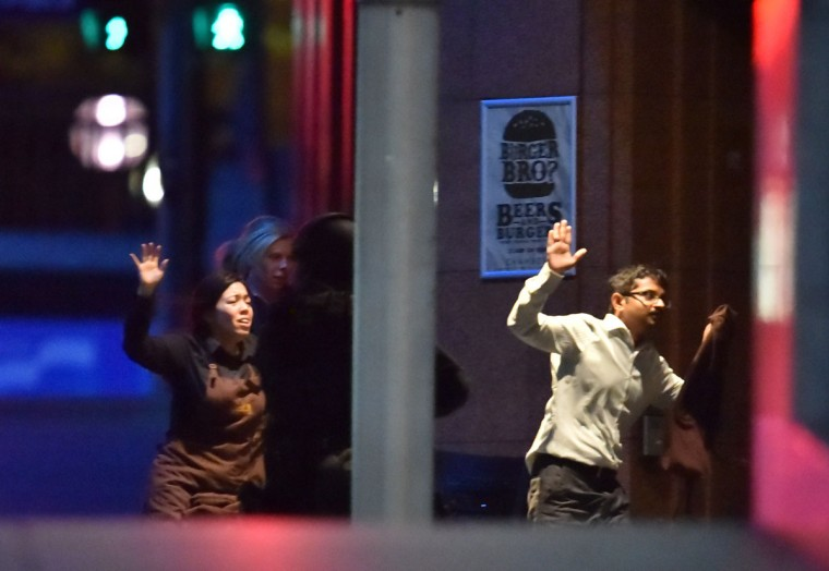 Hostages run out of a cafe in the central business district of Sydney on December 16, 2014. Police stormed the Sydney cafe where a gunman had taken hostages and displayed an Islamic flag, television footage showed early December 16. (PETER PARKS/AFP/Getty Images)