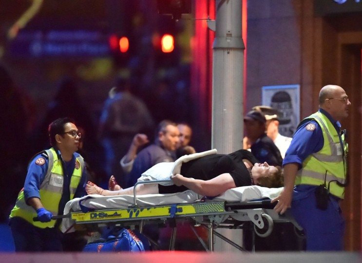 An injured hostage is carried out of a cafe in the central business district of Sydney on December 16, 2014. Police stormed the Sydney cafe where a gunman had taken hostages and displayed an Islamic flag, television footage showed early December 16. (PETER PARKS/AFP/Getty Images)