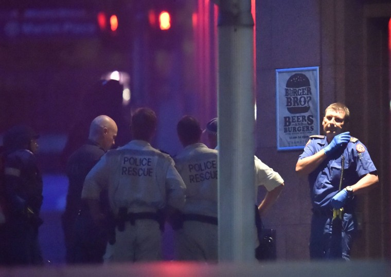 Australian police carry out a hostage rescue from a cafe in the central business district of Sydney on December 16, 2014. Police stormed the Sydney cafe where a gunman had taken hostages and displayed an Islamic flag, television footage showed early December 16. Police have confirmed the siege is over. (PETER PARKS/AFP/Getty Images)