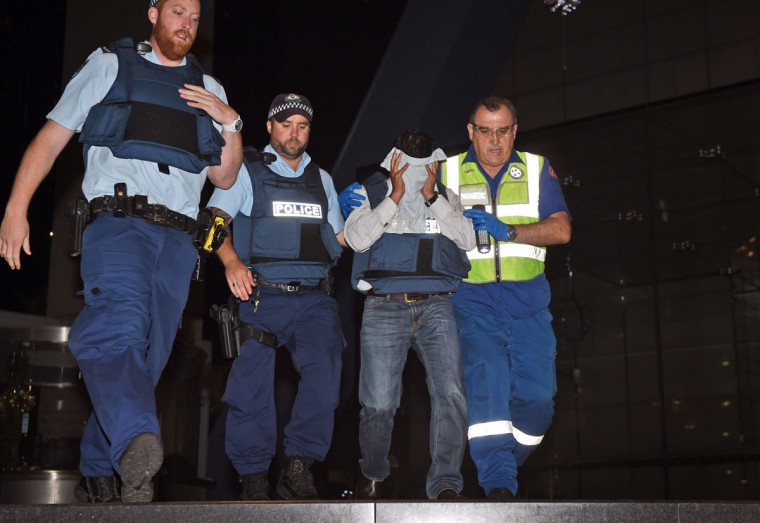Police escort a hostage (second right) with the help of a paramedic (right) during a hostage siege in the central business district of Sydney on December 16, 2014. Police stormed the Sydney cafe where a gunman had taken hostages and displayed an Islamic flag, television footage showed early December 16. At least two people were killed, television reports said early Tuesday. (WILLIAM WEST/AFP/Getty Images)