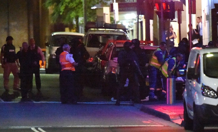 Armed police and paramedics take out injured people following an operation at a cafe in the central business district of Sydney on December 16, 2014. Police stormed the Sydney cafe where a gunman had taken hostages and displayed an Islamic flag, television footage showed early December 16. (SAEED KHAN/AFP/Getty Images)