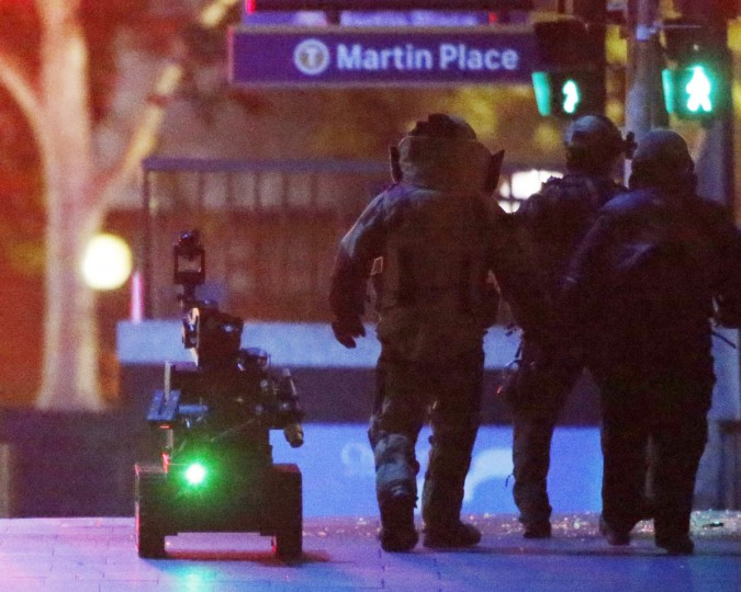 Police officers wearing armored suits walk with a robot towards Lindt Cafe in Martin Place in central Sydney on December 16, 2014.(REUTERS/Jason Reed)