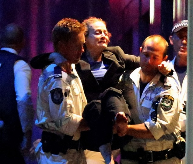 A woman is carried out by police from the Lindt Cafe, Martin Place following a hostage standoff on December 15, 2014 in Sydney, Australia. Police stormed the Sydney cafe as a gunman had been holding hostages for 16 hours. (Photo by Joseph Martinson/Getty Images)