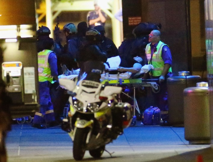 A woman is taken to an ambulance by stretcher outside Lindt Cafe, Martin Place on December 15, 2014 in Sydney, Australia. Police attend a hostage situation at Lindt Cafe in Martin Place. (Photo by Don Arnold/Getty Images)