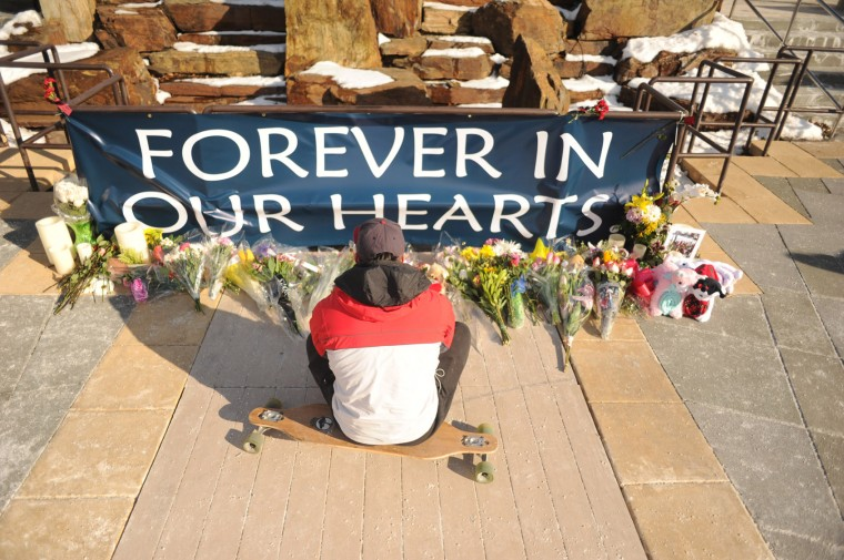 Tyler Bohn of Mt. Airy, a former employee of Zumiez, and good friend of Brianna Benlolo, sits on his longboard thinking about her in front of a memorial life in her memory at the Mall in Columbia on Monday, Jan 27. Benlolo, one of the two shooting victims, inspired Bohn to start longboarding. (Brian Krista/BSMG)