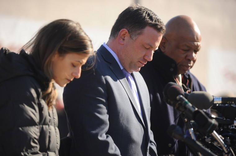 County executive Ken Ulman, center, along with his wife Jaki Ulman, left, and U.S. Congressman Elijah Cummings pause for a moment of silence in front of a memorial honoring the lives of the shootings victims at the Mall in Columbia on Monday, Jan 27. (Brian Krista/BSMG)