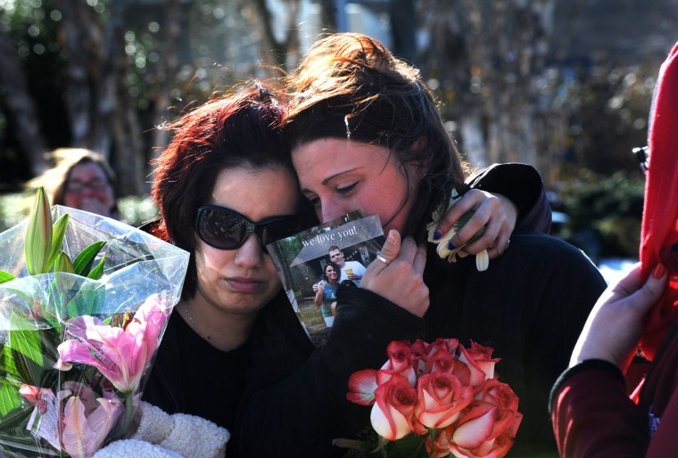 Mourners bring flowers to The Mall in Columbia after it reopens after the weekend shootings. Photo by Algerina Perna/Baltimore Sun