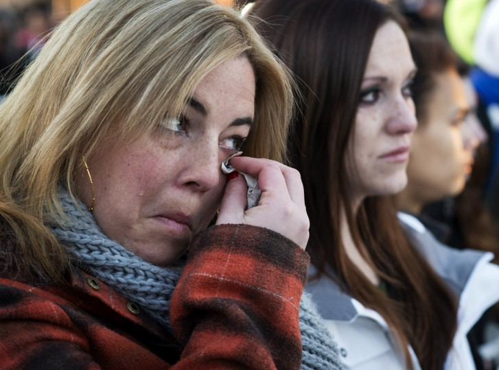 Kerri Nussbaum (left) wipes at her tears Thursday, Jan. 30, 2014, as she and coworker Sami Hurst attend a vigil for Brianna Benlolo and Tyler Johnson, the Zumiez store employees shot and killed by Darion Marcus Aguilar, who then took his own life. The two work at Cavallero and Company, located on the second level across from the store where the shootings occured. (Christopher T. Assaf/Baltimore Sun staff)